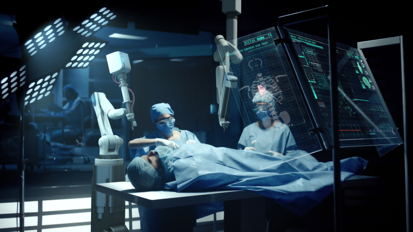 Team of Surgeons Perform a Delicate Operation using a Double Arm Medical Surgical Robot while Observing Data on Transparent Screens. Modern Medical Equipment. Robotic Arm for Minimal Invasive Surgery.