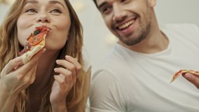 Cropped view of a couple man and woman eating pizza and smiling