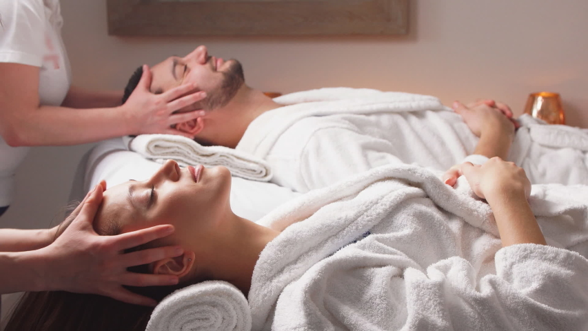 Charming modern couple enjoying a face massage in wellness salon. Relaxing and health.