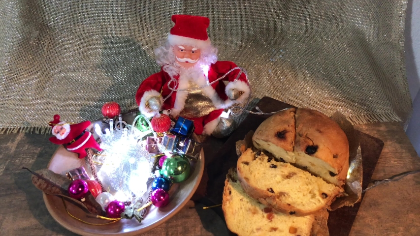 Christmas light with Santa Claus in the blurred background. Foreground, panettone, decorating Brazilian Christmas table. Selective focus. Dark background. Close view.