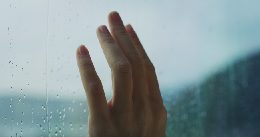 Close up of a young woman hand is touching a glass with water drops while outside is raining.