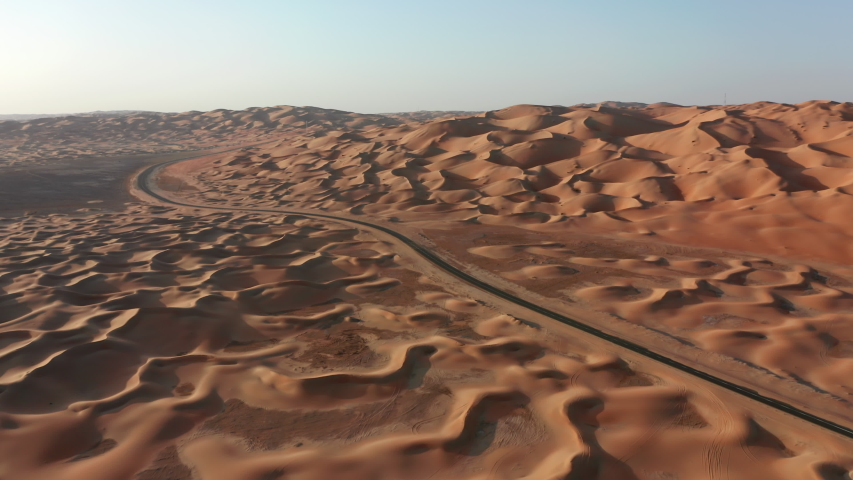 Aerial drone shot of empty road in a desert. Sunset time with vivid colors and deep shadows. Emirate of Abu Dhabi, Liwa desert. Cinematic 4k footage   Shutterstock HD Video #1041913177