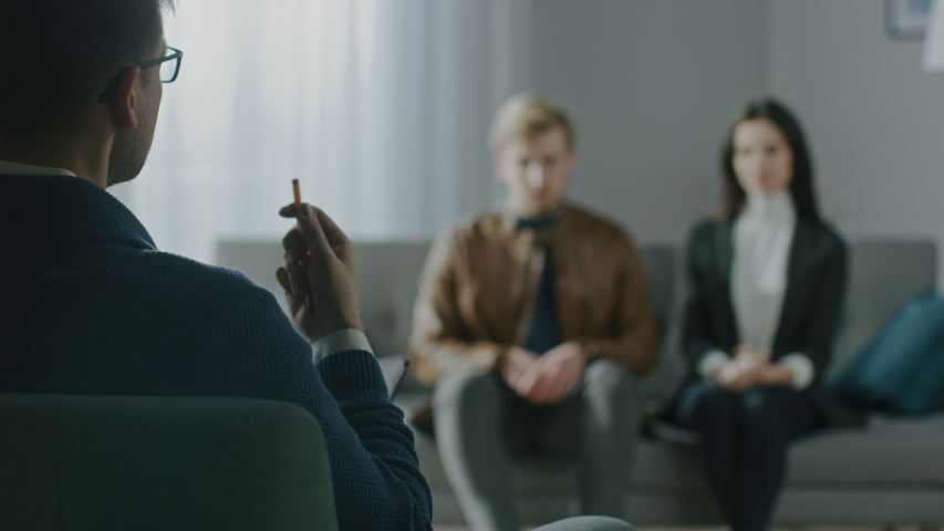Unfocused Couple on a Counseling Session with Psychotherapist. Foreground Focus on Back of the Therapist Taking Notes and Talking: People Sitting on the Analyst Couch, Discussing Relationship  Royalty-Free Stock Footage #1041916768