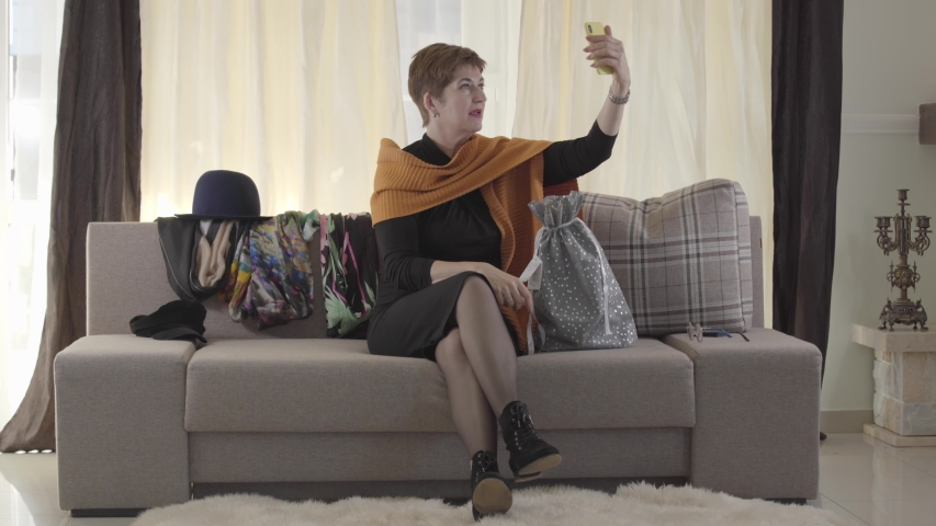 Adult attractive Caucasian woman talking to subscribers via smartphone. Pretty lady sitting on sofa with gift bag and recording selfie video blog. Online technologies, blogging. | Shutterstock HD Video #1041923473