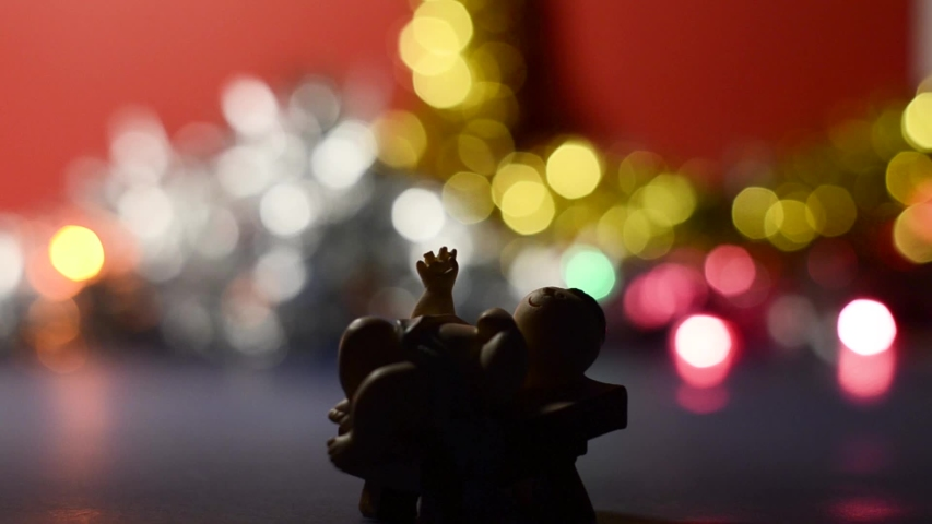 Decorative figure of Baby Jesus with shooting star light effect and bokeh effect in the background | Shutterstock HD Video #1041927043