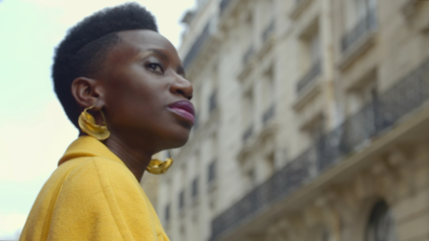 Beautiful African woman looking out at city confidently while she waits on transportation. Portrait of gorgeous fashion model looking boldly outward as she travels in Paris, France. 4K, CU, slow-mo. | Shutterstock HD Video #1041933124