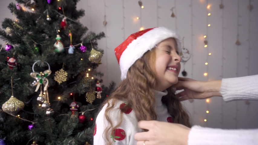 Mom puts a Santa Claus hat on the baby. The girl laughs and fools around. preparation for the new year | Shutterstock HD Video #1041935317