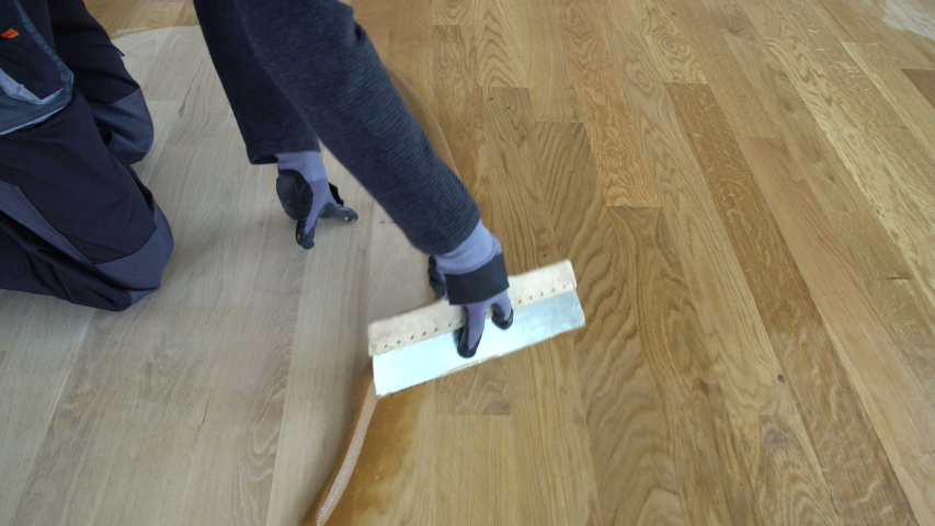 Carpenter master with gloves grouting wooden parquet, phase after sanding. Varnishing of oak parquet floor, man workers with hand and spatula Royalty-Free Stock Footage #1041940996