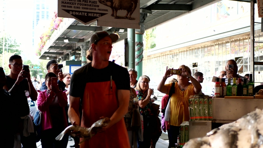 Seattle, Washington/USA: September 08th 2019:  Flying fish: man throwing fish in the air to another man inside the Fish Market in Seattle.