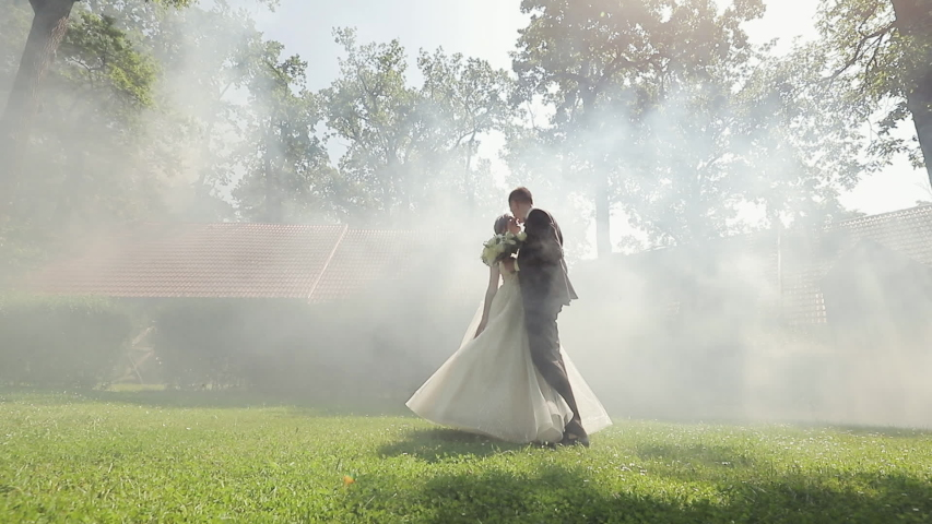Wedding couple walking in the park. Wedding couple walking with beautiful park. Young couple in love at morning, they embrace kiss and look at each other with tenderness.