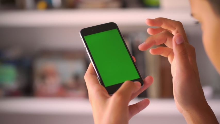 Cute girl teenager swipes down and zooms in green chromakey image on phone in blurry background close view slow motion | Shutterstock HD Video #1041947839