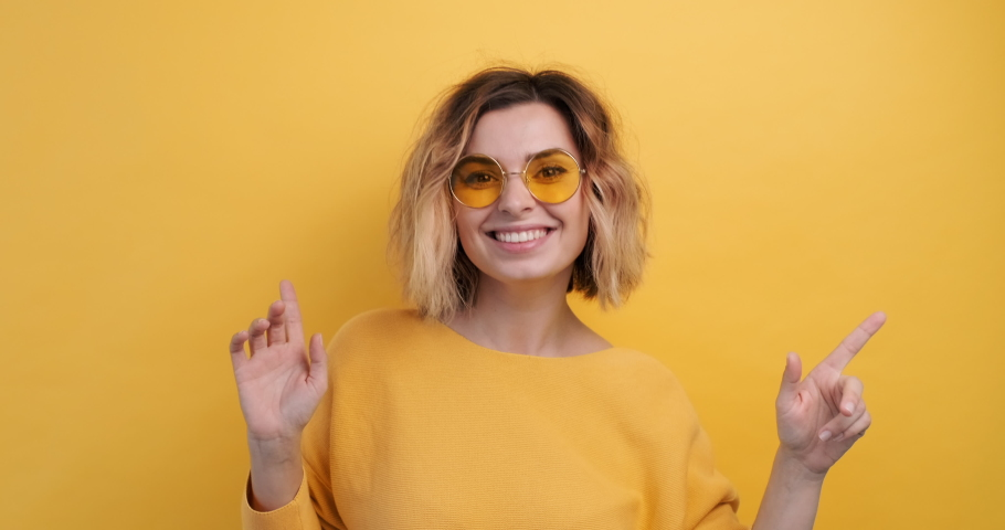 Portrait happy woman in yellow glasses smiling dancing to music rhythmically to beat moving her hands in yellow sweater yellow background slow motion. Monotone. Emotions of people. Teen girl dancing | Shutterstock HD Video #1041950827
