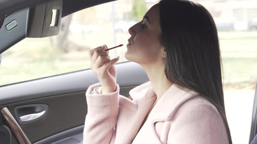 Beautiful woman putting on makeup in car interior