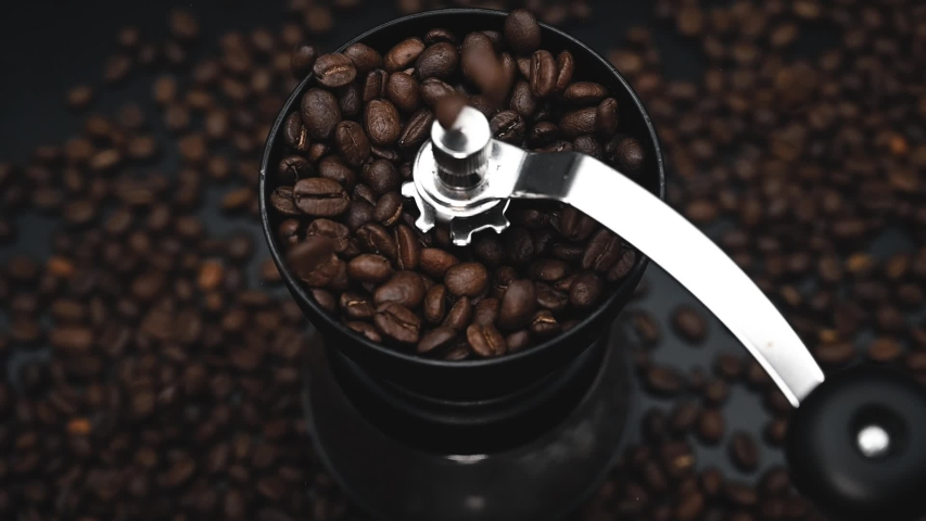 Fried coffee beans are falling to the manual grinder. Cinematic slow motion video. Preparation of fresh beverage morning coffee for breakfast. Mill for grinding. Isolated on black background. | Shutterstock HD Video #1041987490