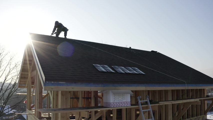 Aerial view builder in safety harness working on the rooftop. Wooden frame house under construction. Bright sunny day