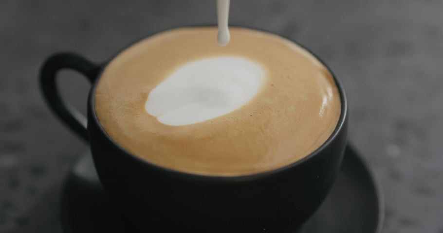 Slow motion pouring steamed milk into cappuccino in black cup on terrazzo countertop #1042001566