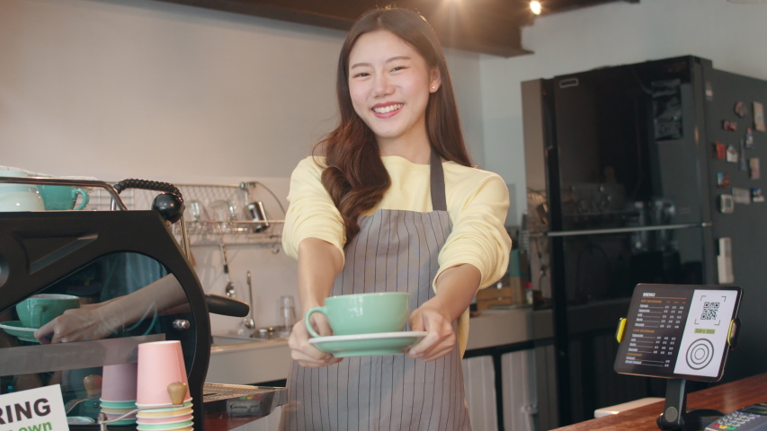 Portrait young Asian lady barista waitress holding coffee cup feeling happy at urban cafe. Asia small business owner girl in apron relax toothy smile looking to camera stand at counter in coffee shop.