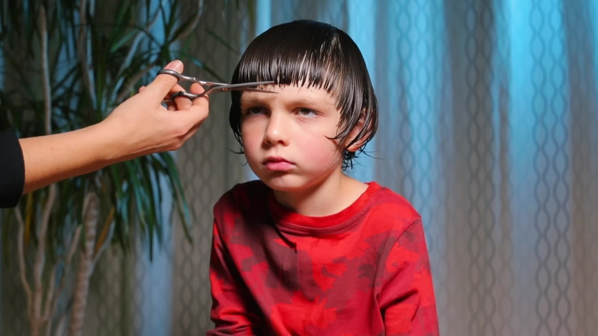 Hair cutting at home. Epidemic of coronavirus infection COVID-19. Hairdressers are closed.A serious child on a haircut by a hairdresser. A boy in red clothes is scissored by cutting bangs on his head.