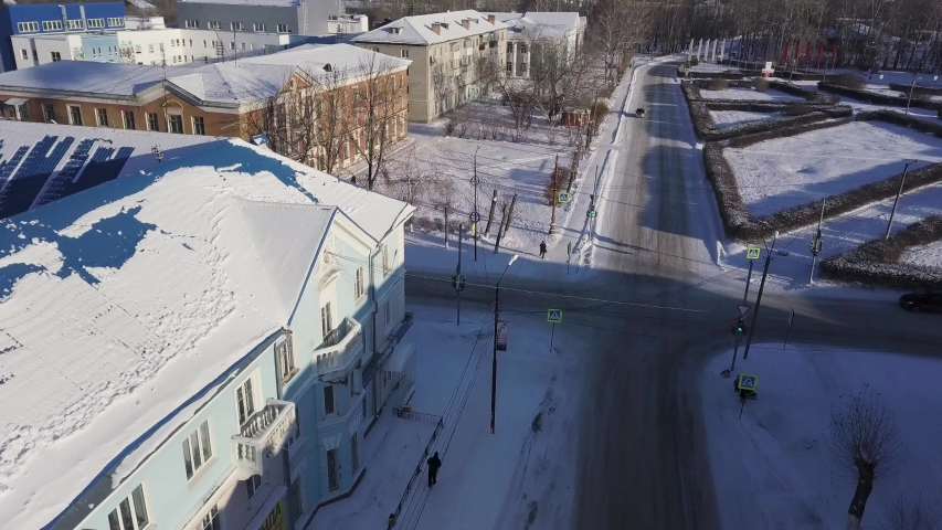 Aerial view of small town during winter with a snowy road and a driving car. Stock footage. Calm life in a beautiful town, many houses and buildings covered by snow.