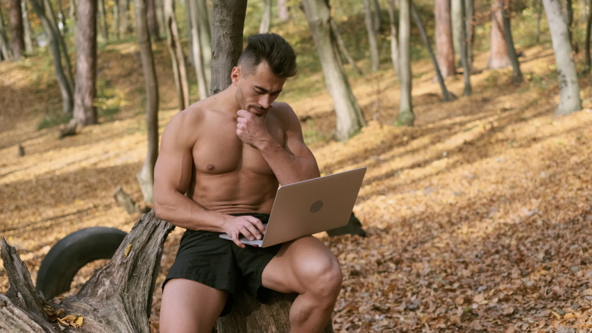 Strong Naked Torso Guy Sits In An Autumn Park With Laptop In His Hands. Guy Scratches His Chin Thoughtfully. | Shutterstock HD Video #1042044121
