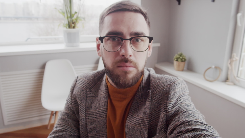 Chest-up shot of bearded Caucasian man in hipster glasses, blazer and turtleneck sitting in office, holding invisible smartphone in extended hand and having personal conversation on video call
