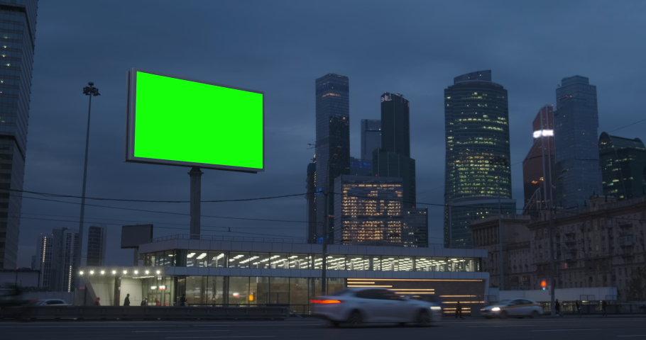 Large billboard with a green screen, a megapolis highway with neon lights, skyscrapers on background, city traffic at night, Moscow Russia Royalty-Free Stock Footage #1042054993
