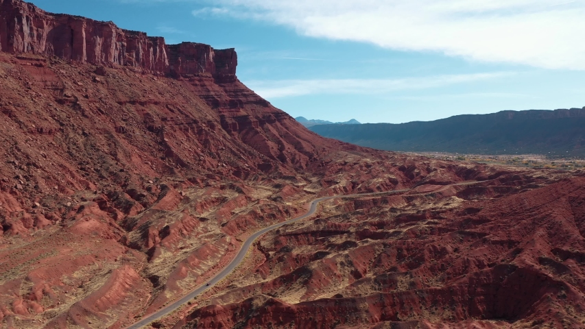 High monument of red rocks buttes of canyon in valley of colorado river in western Usa. Colorful landscape of desert nature with sand dunes and sandstone erosion. Aerial motion back and slow turn left   Shutterstock HD Video #1042057216