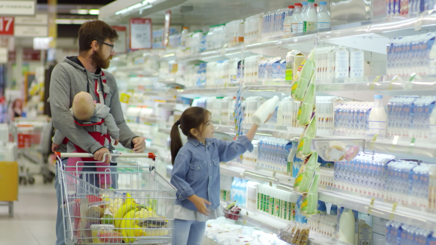 Front view of young bearded man in glasses carrying baby in sling and pushing shopping trolley along supermarket aisle, daughter of primary school age helping him | Shutterstock HD Video #1042063573