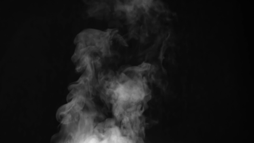 White Steam Rises Over the Hot Pan. White Steam rises from a large pot that is behind the scenes. Black background. Filmed at a speed of 120fps #1042064089