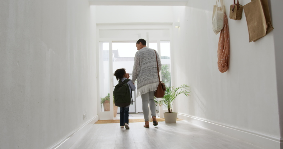Rear view low angle of a young African American girl and her mother leaving home, talking and holding hands as they walk in the sunlit corridor towards the front door, slow motion