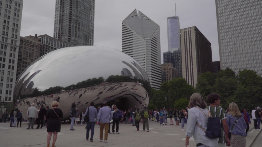Chicago, USA - Circa 2019: Famous cloud gate art sculpture in downtown park made of steel reflecting cityscape skyline on Chicago bean day time exterior establishing shot skyline in background | Shutterstock HD Video #1042070746