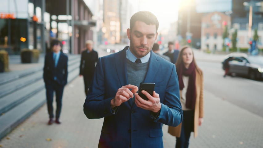 Caucasian Businessman in a Suit is Using a Smartphone on a Street in Downtown. Other Office People Walk Past. He Smiles and Looks Successful. He's Browsing the Web on his Device.