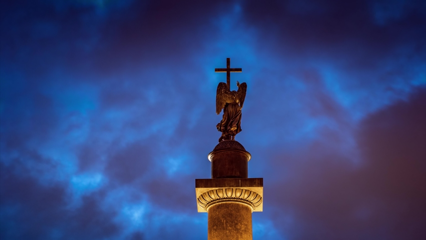 Storm clouds moving behind statue of angel holding a cross on top of historic Alexander Column (built between 1830-1834) in Saint Petersburg, Russia. Timelapse, 4K UHD.