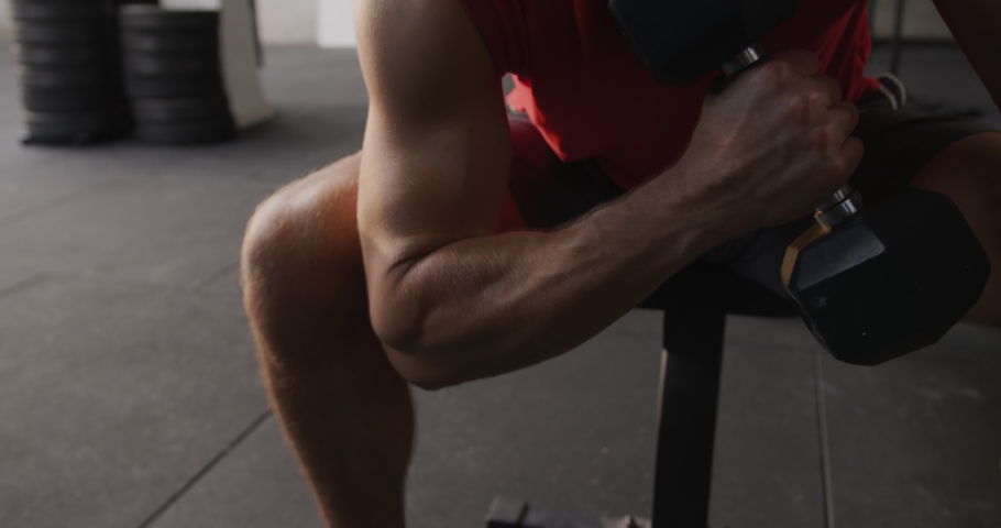 Front view close up of an athletic Caucasian man wearing sports clothes cross training at a gym, sitting and doing curls with a dumbbell, slow motion #1042081621