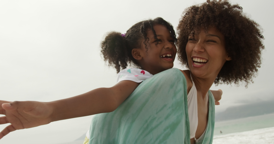 Side view close up of an African American woman in standing by the sea piggybacking her young daughter who has her arms outstretched, both smiling, slow motion