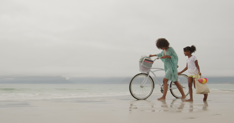 Side view of a smiling African American woman walking with her young daughter and wheeling a white bike along a beach by the sea, slow motion