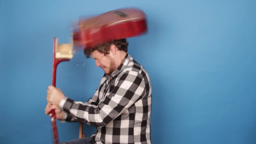 A mad man hits himself on the head with a guitar. The guy breaks a guitar on his head on a blue background. | Shutterstock HD Video #1042089466