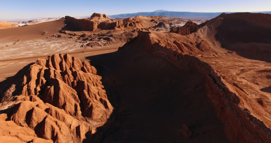 The flight over the dune ridge in Moon Valley. Fantastic landscape of Atacama desert. Panoramic view of vast arid terrain and erosion formations. San Pedro de Atacama. Chile. Aerial. 4K