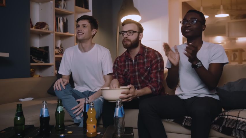 Happy multiethnic young male sport fans shout watching football game together at home with snacks slow motion. | Shutterstock HD Video #1042098094