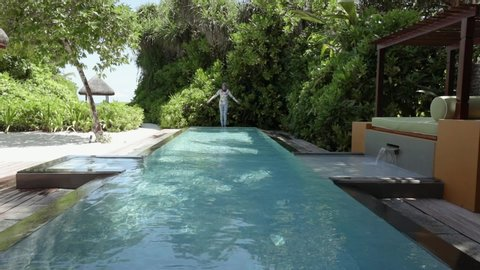 Landaa Giraavaru , Baa Atoll / Maldives - 09 18 2018: A woman jumps into a long rectangular pool at luxury villa resort in the Maldives.