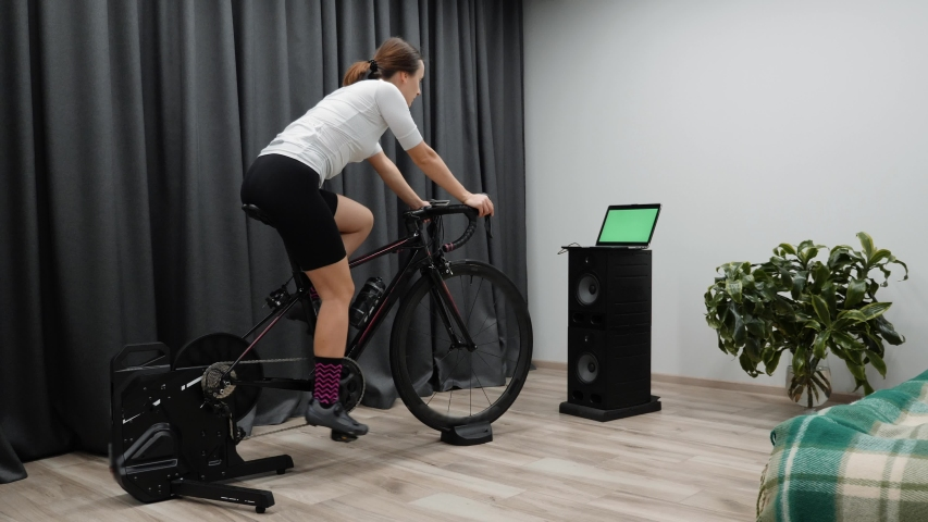 Cycling woman on smart trainer. Fit caucasian female training on bicycle looking at computer screen racing online.