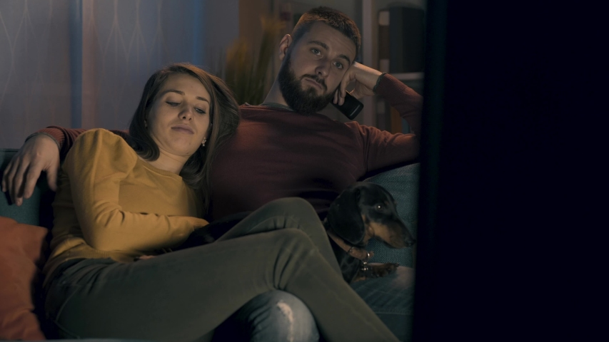 Tired bored couple relaxing on the sofa with their dog and watching TV shows | Shutterstock HD Video #1042113046