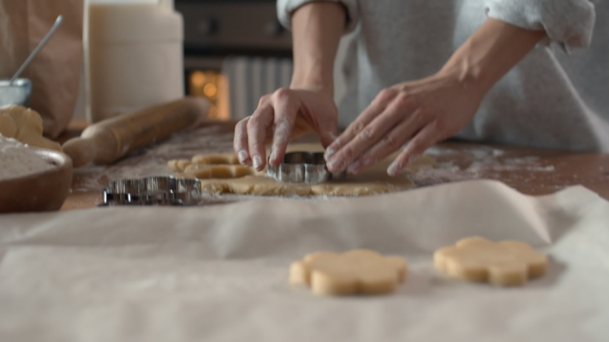 Close up of female baker hands making biscuits using baking tin in shape of flower | Shutterstock HD Video #1042113112