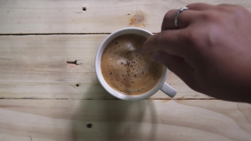 Top view of Person hand steering coffee in a cup with spoon. Breakfast morning of a cup hot black coffee on wooden background. footage b-roll scene 4k. home making coffee.