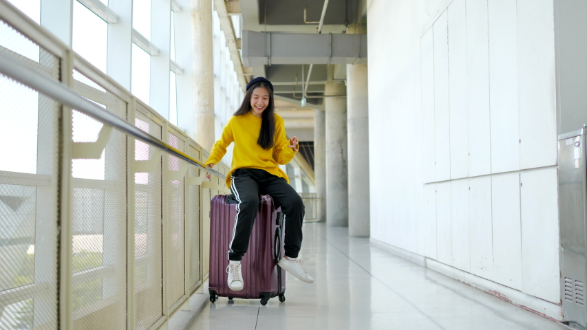 Joyful young woman wearing casual clothes sitting on her luggage and waiting for her flight. | Shutterstock HD Video #1042114657