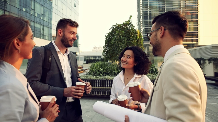 Group of coworkers having a coffee brake together, standing outside in front of office buildings and talking. | Shutterstock HD Video #1042117333