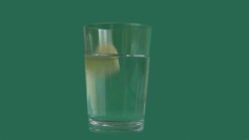 Effervescent vitamin C tablet dissolving in the glass of water on the green screen. Slow motion.  | Shutterstock HD Video #1042129879