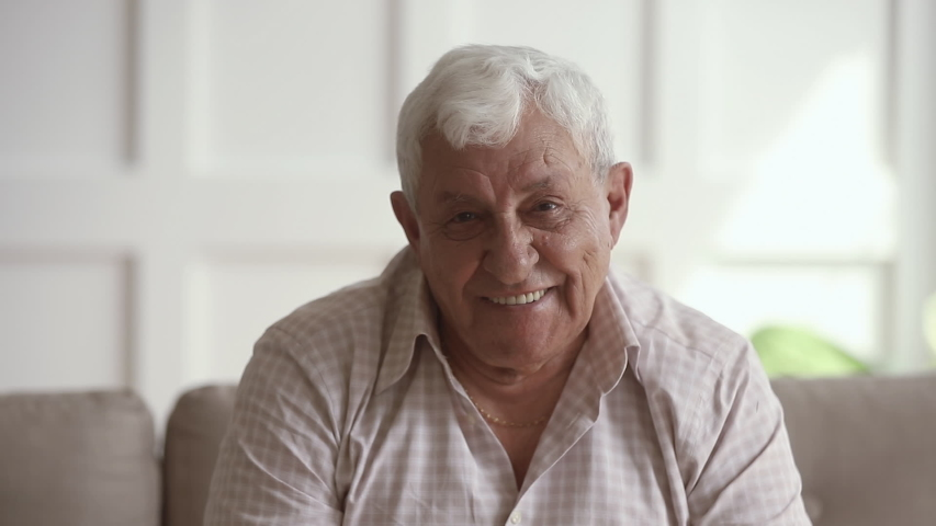Cheerful elderly 80s man looking at camera. Happy mature grandfather listening to joke, having fun, laughing, sitting on comfortable couch at home. Excited healthy grandpa hearing good news. | Shutterstock HD Video #1042130731