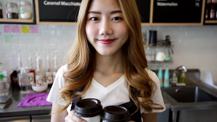 Beautiful Smiling AsianWoman Passing Coffee Cups To Go Toward Client Happy Barista. Owner Young Entrepreneur Passion .Small business owner Korean girl in apron relax toothy smile looking.