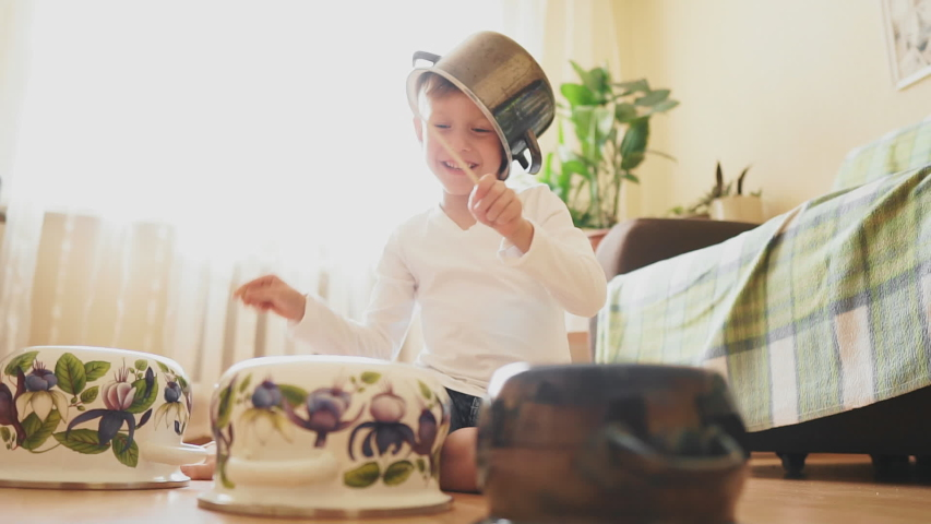 Funny drum part from a little boy. Fun and educational activities for creative kids at home. A little boy plays a drum with a pot on his head | Shutterstock HD Video #1042137874